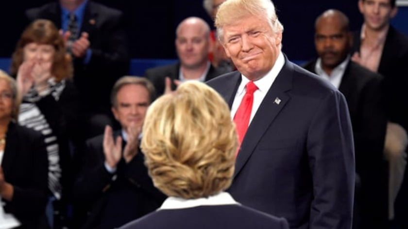 Second US Presidential Debate - Body Language Analysis - Donald Trump and Hilary Clinton did not shake hands at the beginning of the debate, only at the end. Here Trump fakes a smile with a grin of holding back his words and emotions with his lips cursed as he attempts to be civil and courteous