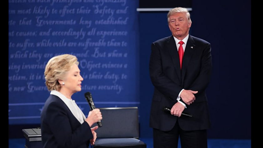 Second US Presidential Debate - Body Language Analysis - Donald Trump stands tall and confident while also holding his left arm with his right hand suggesting strength and self armament . His facial gestures suggest that he is mocking Clinton